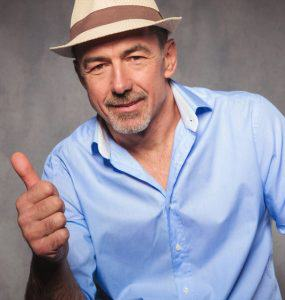 portrait of smart casual man wearing a hat while looking at the camera and showing the ok thumbs up sign